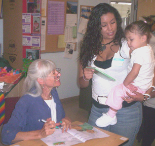 This is a photograph of Judi signing a poster for a Project LIFT mother and child.